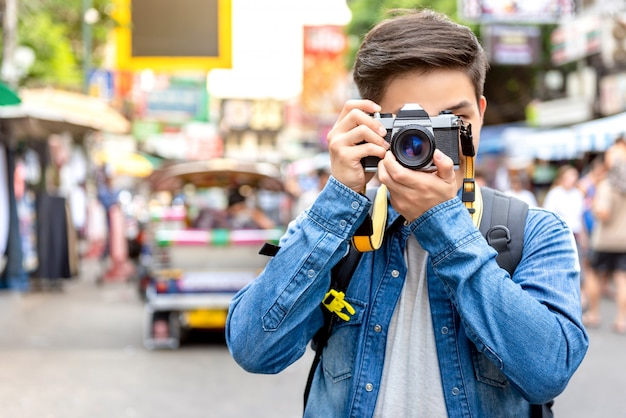Asian man tourist photohrapher taking photo in bangkok thailand