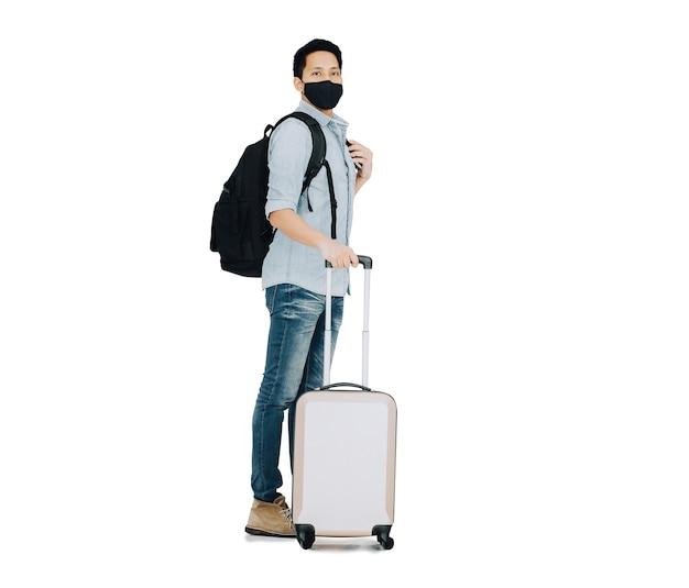 背景で隔離の荷物と立っているフェイスマスクを身に着けているアジア人男性