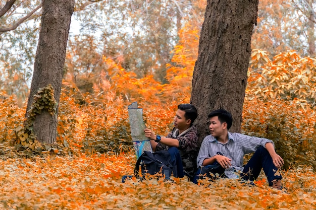 Asian man tourists with backpack to the forest season autumn looking at map to learn hiking trails.