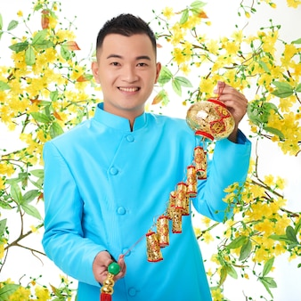 Asian man in traditional jacket posing with colorful lantern, surrounded by blooming mimosa