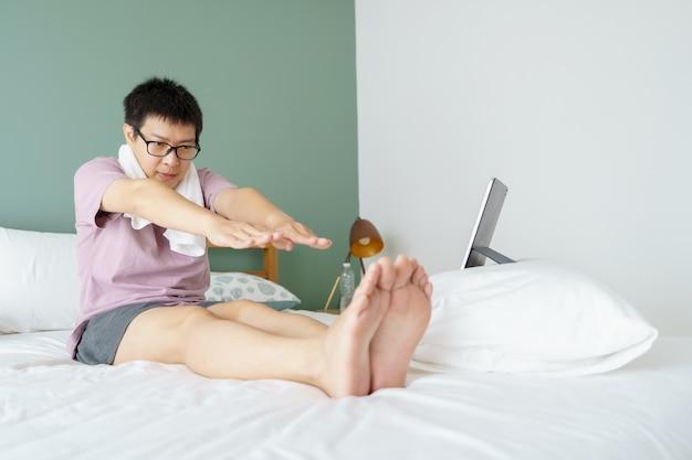 Азиатский мужчина тренируется дома, смотрит видео на планшете