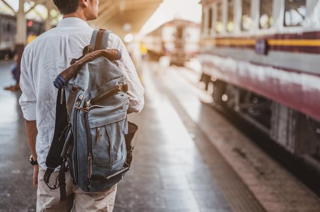 Азиатский путешественник мужчина с рюкзаком на железной дороге, рюкзак на вокзале с путешественником. концепция путешествия. туристический путешественник человек идет на вокзале.