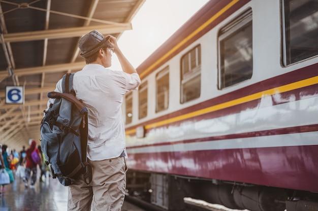 Азиатский путешественник с рюкзаком в ожидании поезда, азиатский турист в шляпе, стоящий на железнодорожной платформе на вокзале бангкока. праздник, путешествие, поездка и лето концепция путешествия.