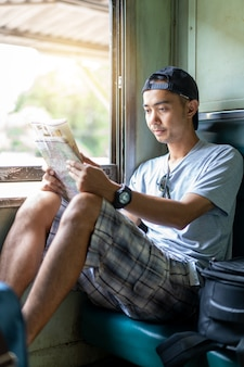 Asian man traveling backpacker reading map sit on the old train seat at thailand
