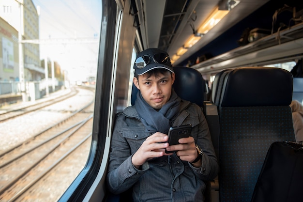 An asian man traveling by railway in europe