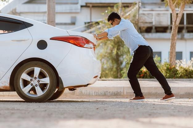 Азиатский мужчина пытается доставить машину в автосервис после разбитой машины. сломанная машина на дороге. аварийная служба разбила машину.