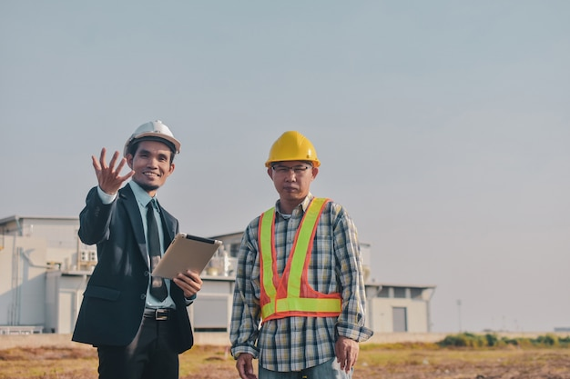 Asian man two people business use tablet check on site construction