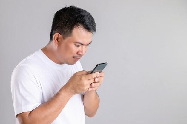 Азиатский мужчина печатает или разговаривает на смартфоне