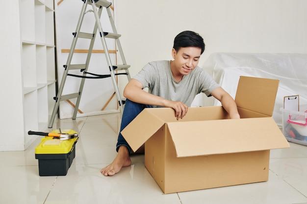 Asian man unpacking tools