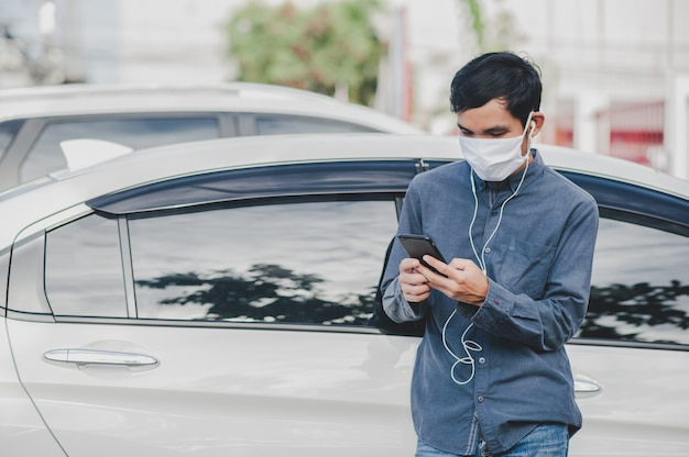 Asian man use face mask are video call on mobile phone standing at car in city focus on phone