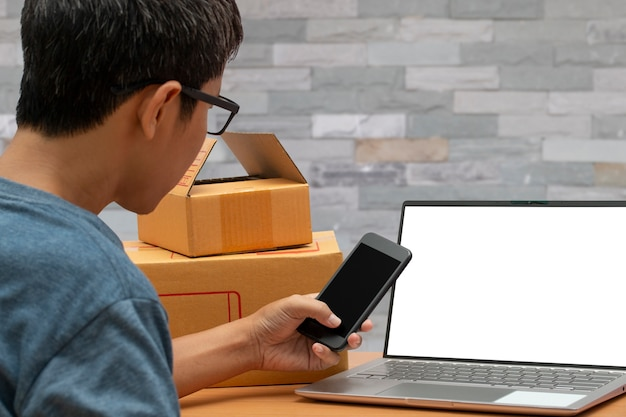 顧客からのオンライン購入の買い物注文をチェックを取るスマートフォンを使用してアジアの男。