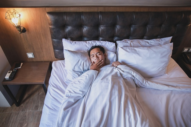 Asian man using blanket yawning while lying on a bed