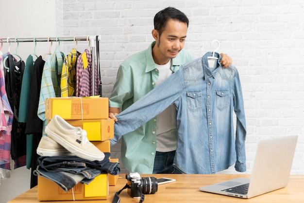 Азиатский мужчина, используя ноутбук, продавая онлайн джинсовые рубашки