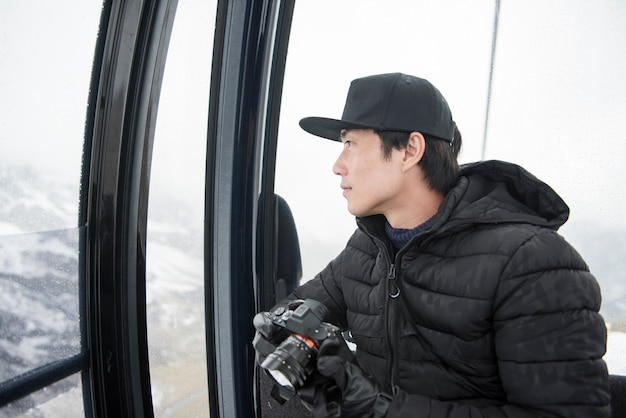 Asian man using his camera while sit in cable car