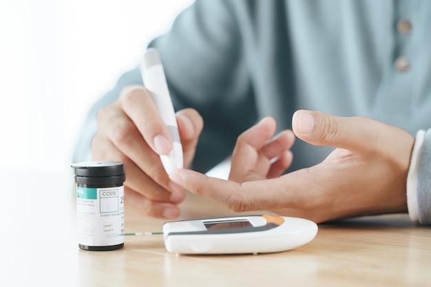 Азиатский мужчина с помощью ланцета на пальце для проверки уровня сахара в крови с помощью глюкометра, здравоохранения и медицины, диабета, концепции гликемии