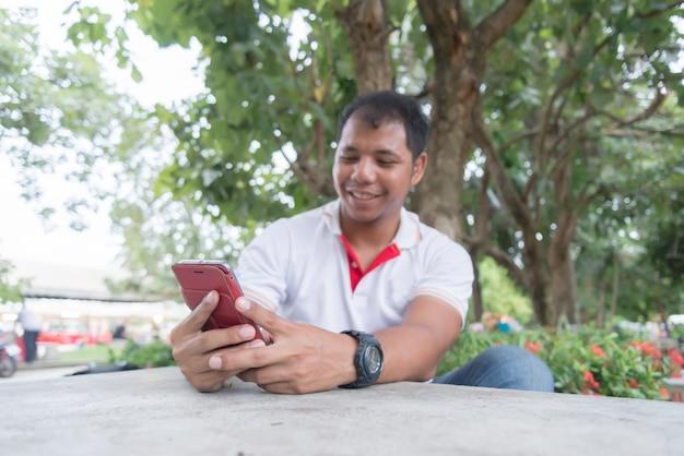 夕方近くの公園のテーブルで携帯電話を使用してアジア人。彼は幸せな瞬間に見えます。モバイルデバイスを働く人々をリラックスの概念。