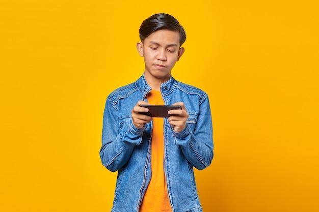 노란색 배경 위에 화난 얼굴로 휴대폰 게임을 하는 아시아 남자