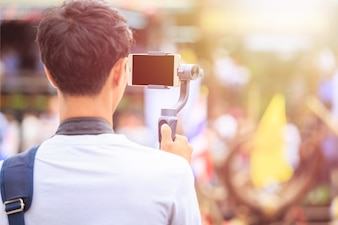 Asian man using modern smartphone record video. Outdoor setup and working