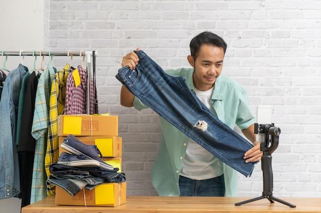 Азиатский мужчина с помощью смарт-мобильного телефона, принимая онлайн продажи джинсов