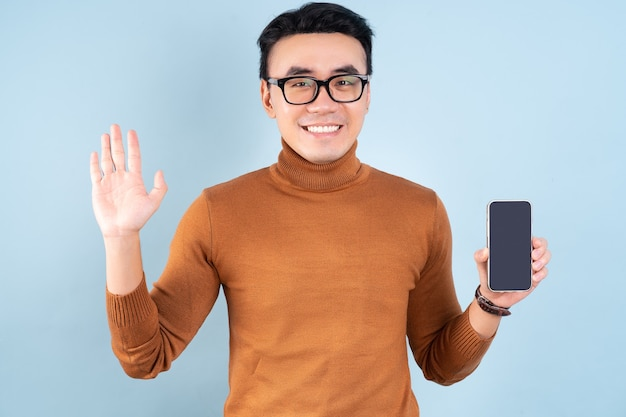 Asian man using smartphone on blue background