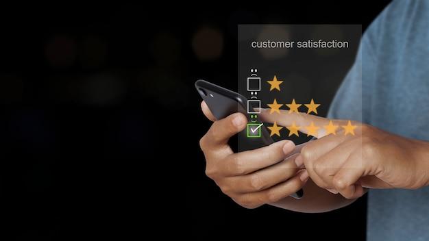 디지털 터치 스크린의 웃는 얼굴 아이콘에 가상 화면이 있는 스마트폰을 사용하는 아시아 남자. 고객 서비스 평가 개념입니다.