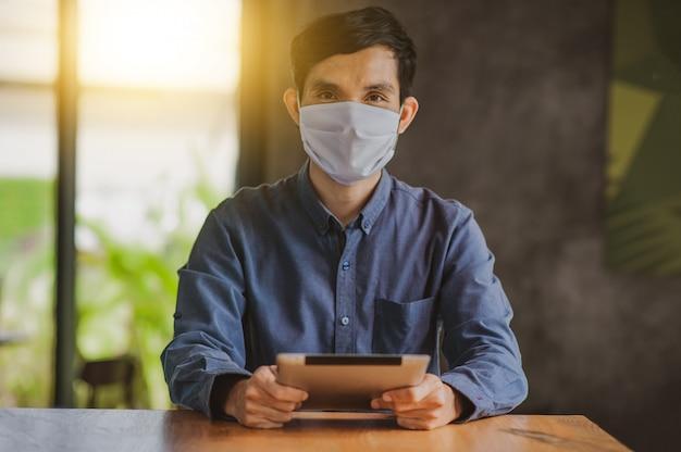 アジア人男性がタブレットを使用してオンラインで身に着けているフェイスマスクを保護し、コロナウイルスのライフスタイルを保護する