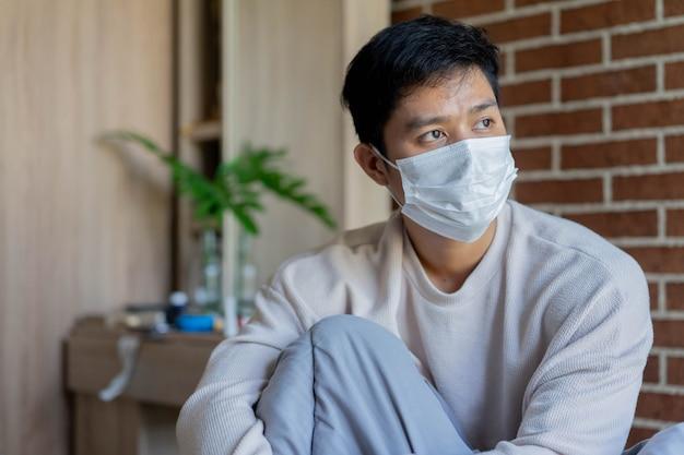 アジア人男性が目を覚まし、隔離時間の朝の寝室でフェイスマスクを着用