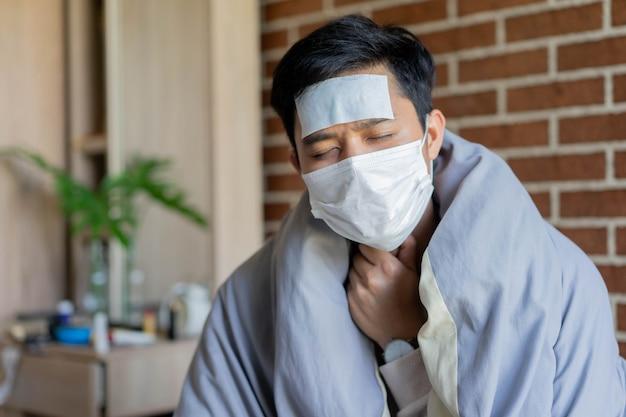Азиатский мужчина просыпается с чувством боли в горле в карантинной зоне спальни для концепции профилактики коронавируса