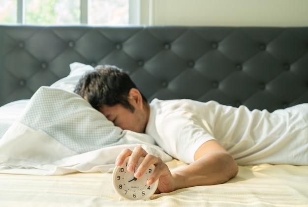 Азиатский человек просыпается утром и рука достигает будильника