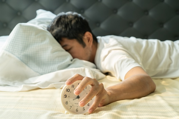 Asian man  wake up in the morning and hand reaching alarm clock