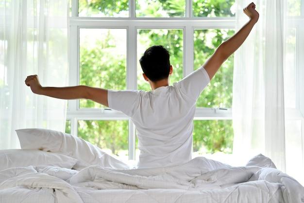 아침에 일어나 침대에 앉아서 스트레칭을 하는 아시아 남자
