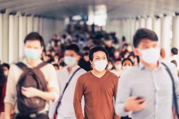 흐릿한 인식할 수 없는 비즈니스 사람들 사이에서 걷고 서 있는 아시아 남자