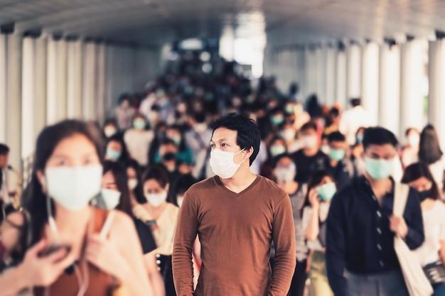 흐릿한 인식할 수 없는 비즈니스 사람들 사이를 걷고 서 있는 아시아 남자