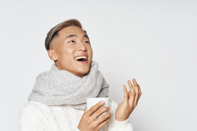 Asian man in warm winter clothes laughing with a coffee cup