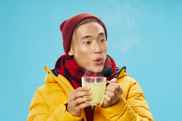Asian man in warm winter clothes posing space on a colored space