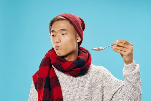 Asian man in warm winter clothes posing in the studio on blue