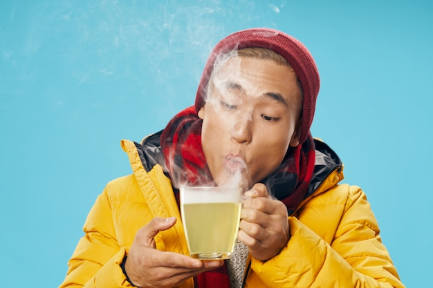Asian man in warm winter clothes posing in the studio on a colored surface