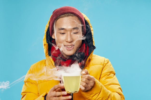 Asian man in warm winter clothes posing in the studio on a colored