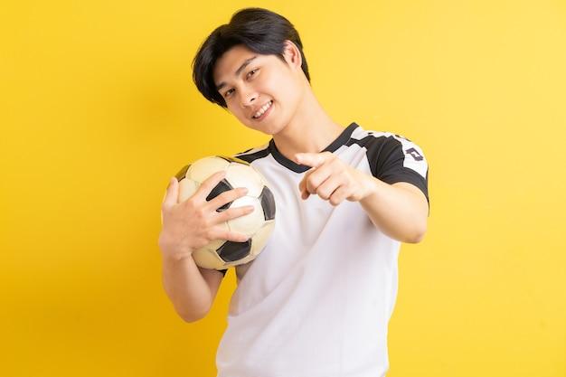 アジア人の男性がボールを持っていて、彼の手を指摘した