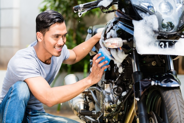 Asian man washing his motorcycle or scooter with soap and sponge