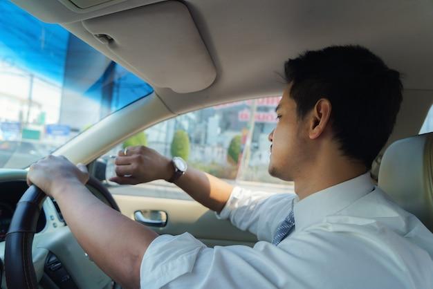 アジア人の男性は、朝遅くに仕事に行くために運転しているときに時計を見ています。