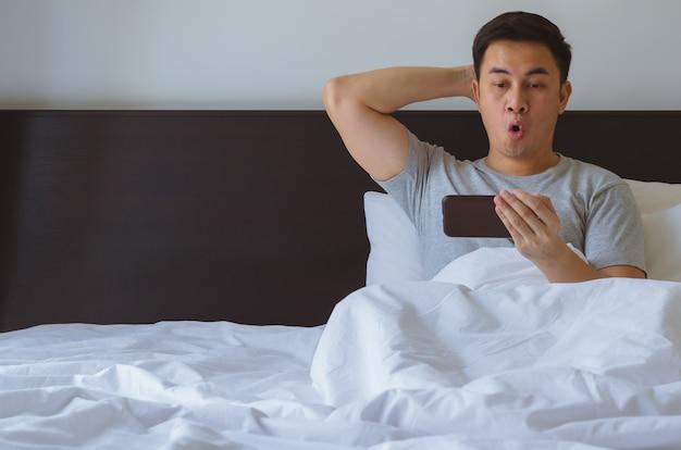 朝ベッドでスマートフォンでオンラインで驚きのニュースを見てアジアの男。