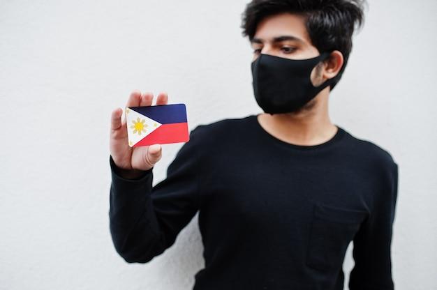 Азиатский мужчина носит все черное с лицевой маской, держит флаг филиппин в руке, изолированной на белом. концепция страны коронавируса.