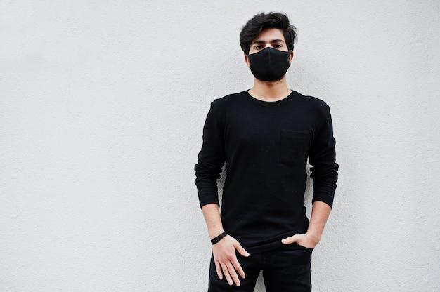 アジア人男性は白で隔離のフェイスマスクですべて黒を着用