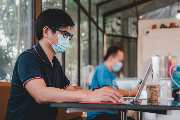 Asian man wear face mask working on laptop computer in coffee shop and keep social distancing from other