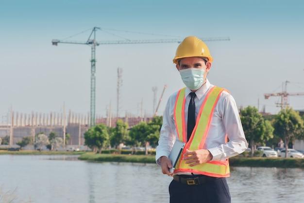 アジア人男性は、サイト建設に取り組んでいるタブレットを保持している医療マスクを着用します
