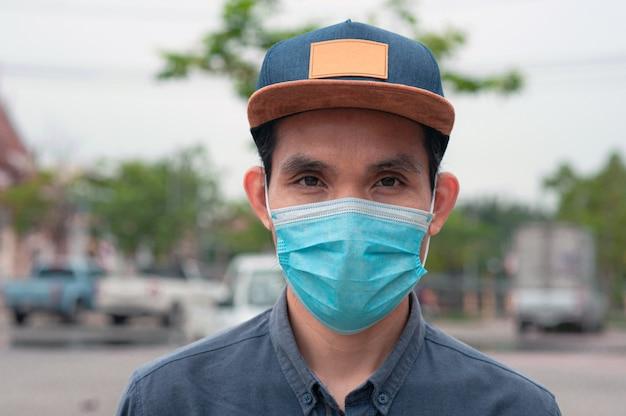 アジア人男性は、コロナウイルスを保護するために新しい通常のライフスタイルで医療用マスクを着用しますcovid 19