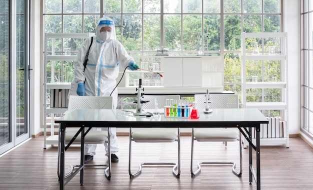 Азиатские мужчины носят индивидуальные защитные костюмы или средства индивидуальной защиты, защитные очки и лицевую маску, что делает дезинфекцию и дезактивацию в комнате лаборатории науки и микробиологии.