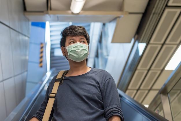 アジア人男性はコロナウイルスを保護するために外科用フェイスマスクを着用し、エスカレーターの上に立ち、地下鉄電車、covid-19コンセプトで街へ旅する