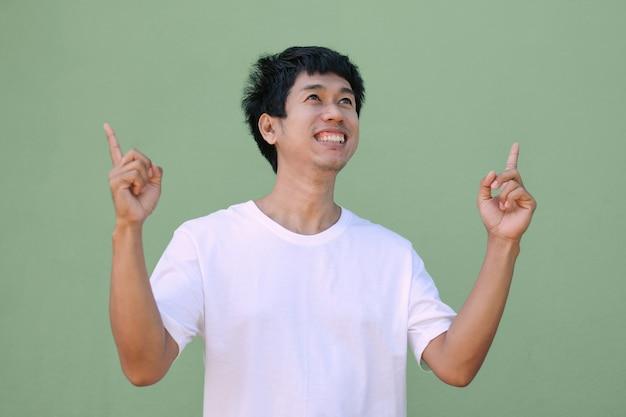 アジア人男性は白いtシャツを着て笑顔を見て、上面図を指しています。孤立したクリッピングパス画像。プロモーションとプレゼンテーション用の画像。